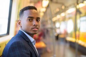 Face of young handsome African businessman sitting inside the train