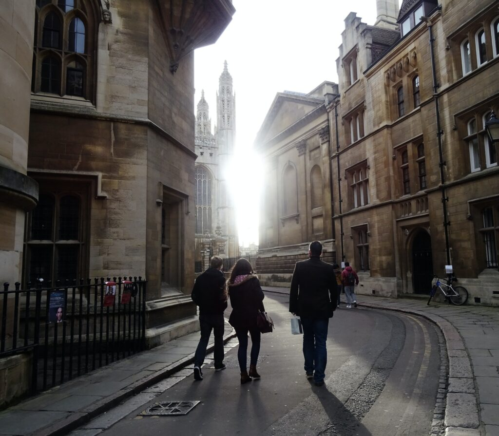 People walking on a street towards bright light, Cambridge, UK.