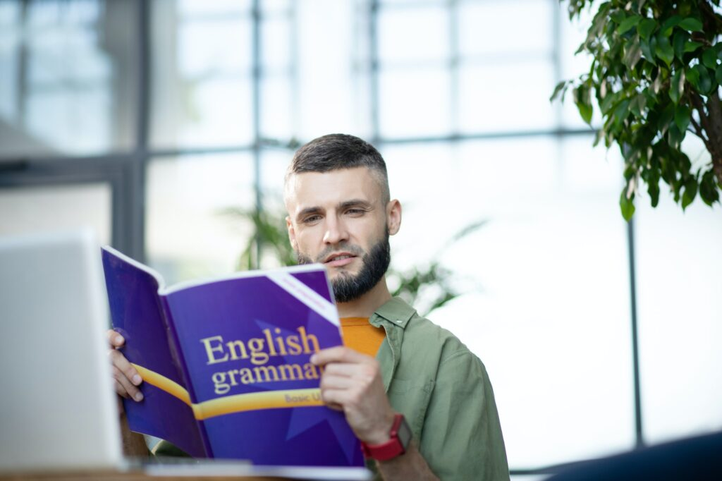 Bearded young businessman studying English grammar