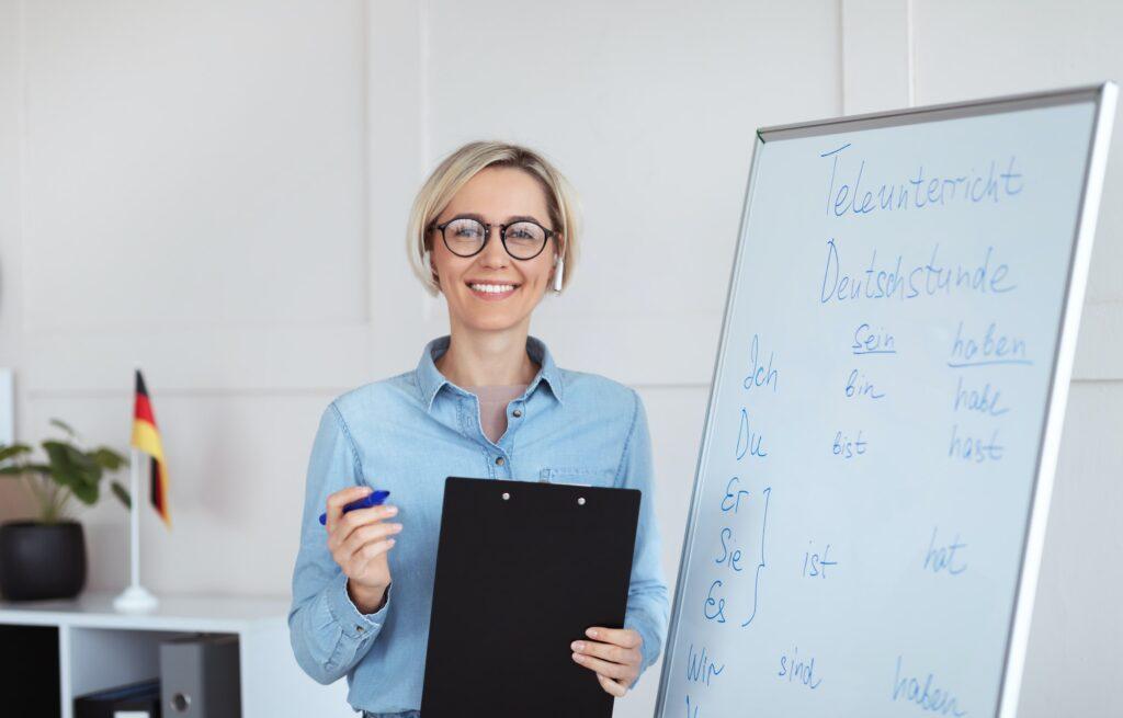 Online schooling. Positive German teacher posing near blackboard with grammar rules, looking at