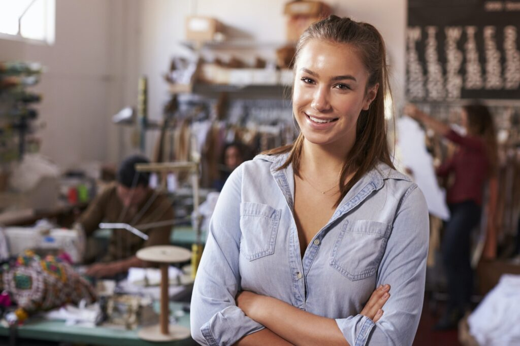 Smiling white female trainee in clothing design studio