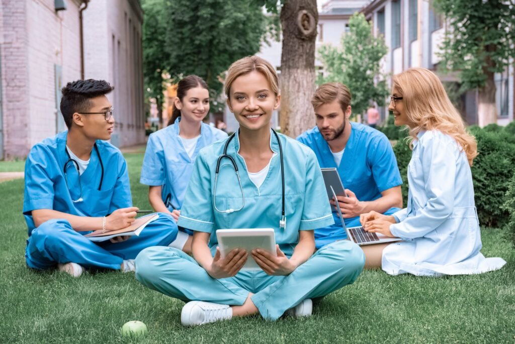 teacher and multicultural students studying outdoors with gadgets at medical university