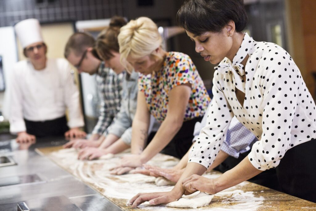 A caucasian male chef teaching a cooking class, multi ethnic group.