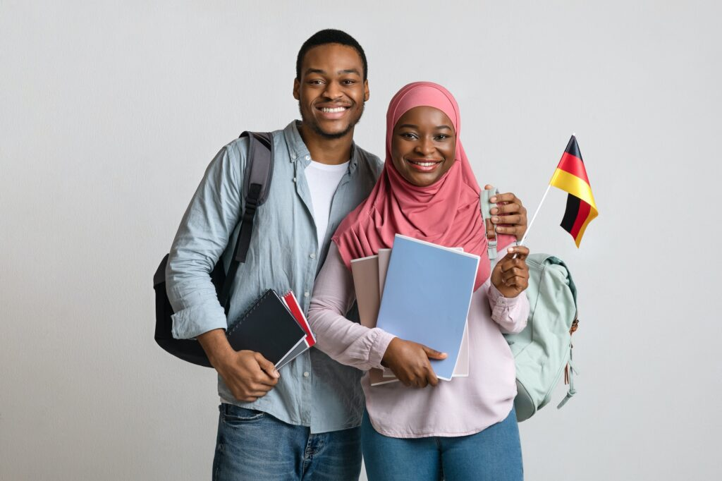 Cheerful african american muslim students couple holding german flag