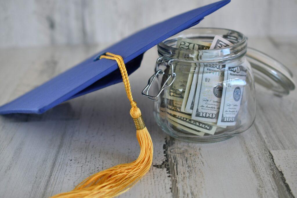 Graduation cap mortarboard with tassel propped on a jar of money cash, concept school loans debt