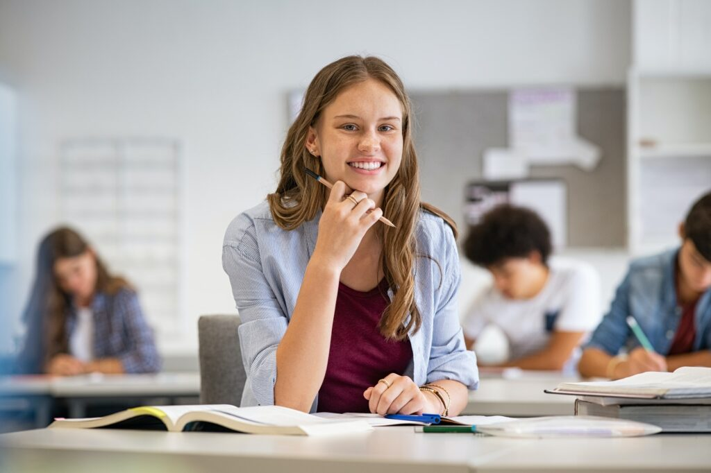 Happy smiling student girl studying in classroom