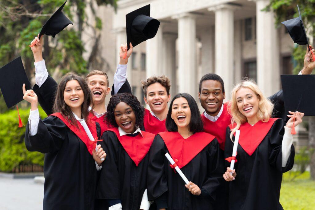 Joyful multiethnic students with diplomas celebrating graduation