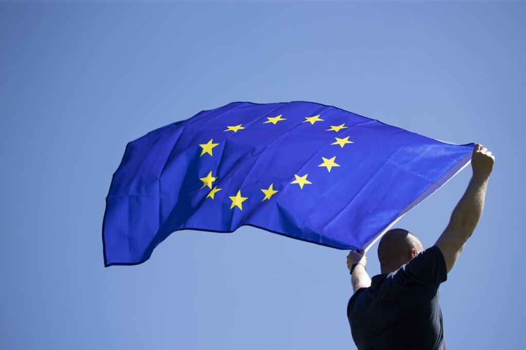 Man with EU flag over blue sky