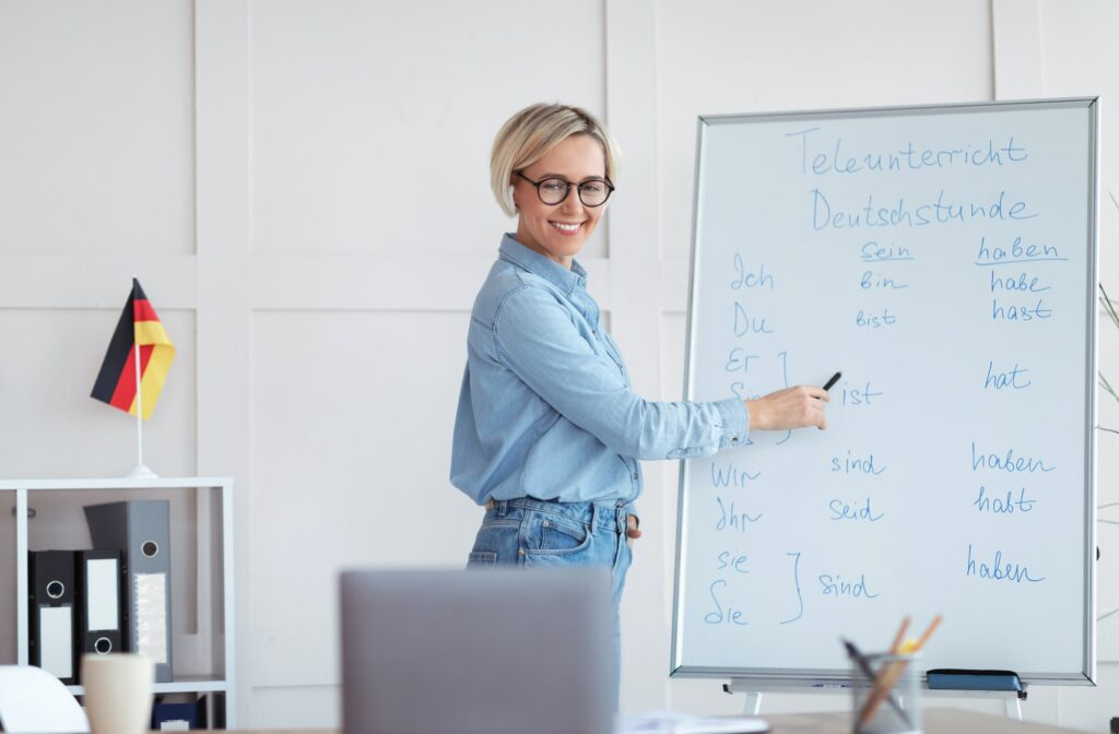 Studying German online. Friendly female teacher giving foreign language lesson online, explaining