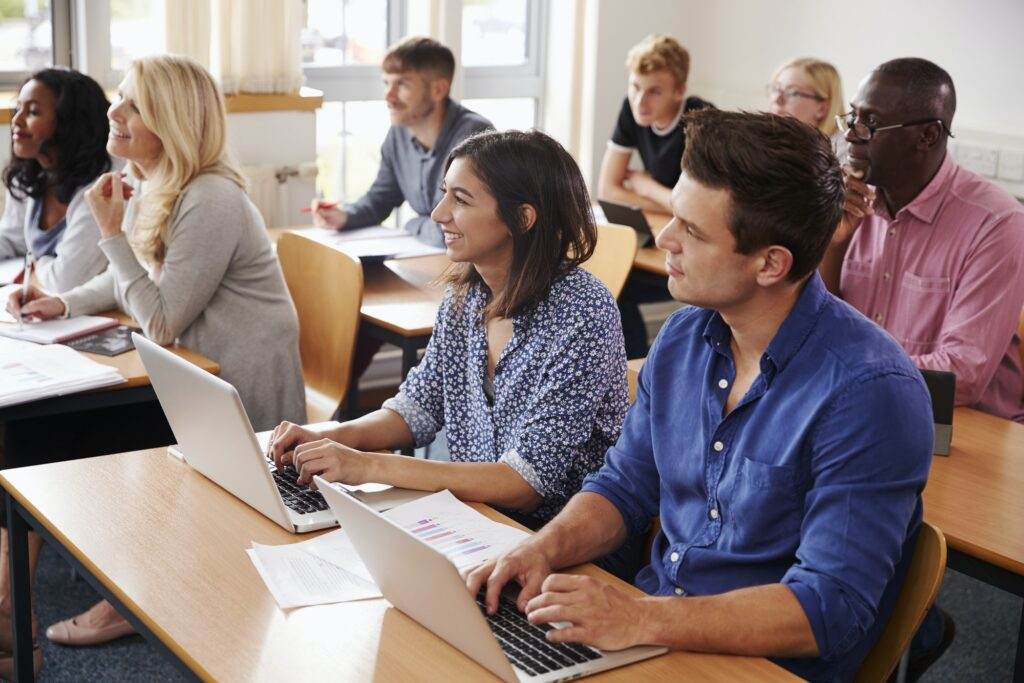Mature Students Sitting At Desks In Adult Education Class