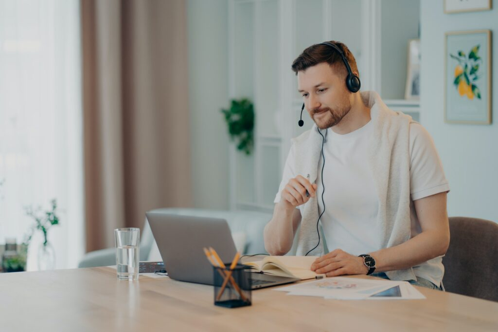 European male student learns foreign languages online has video lesson uses modern headset