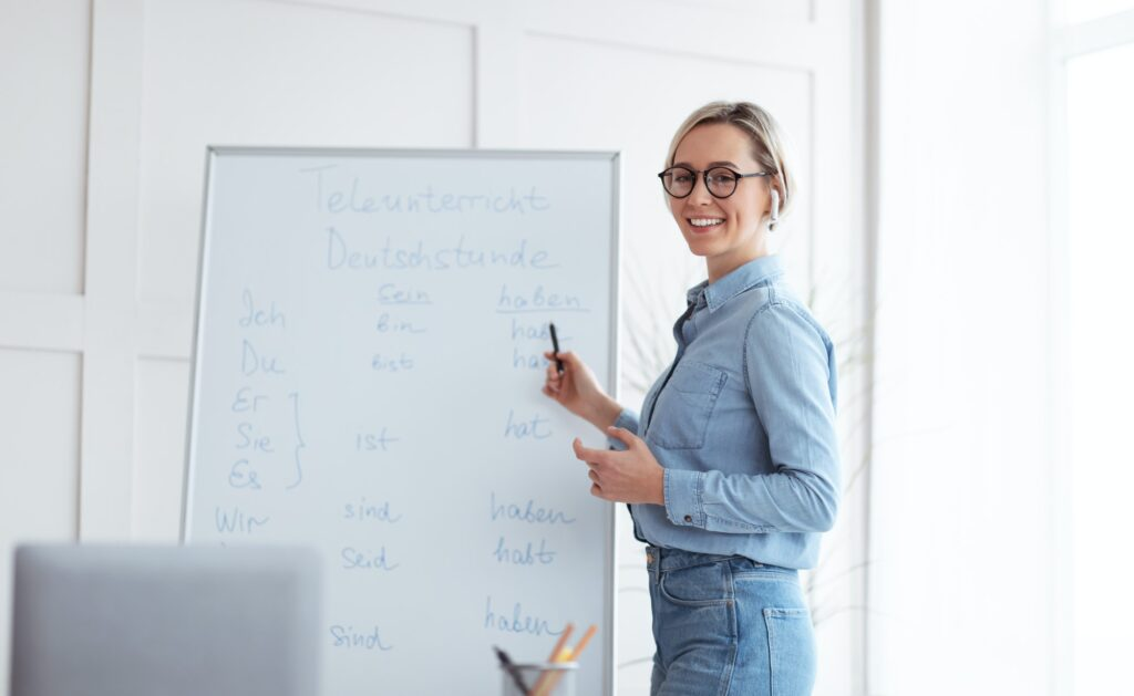 Happy young teacher standing near blackboard and explaining German lesson to students online from