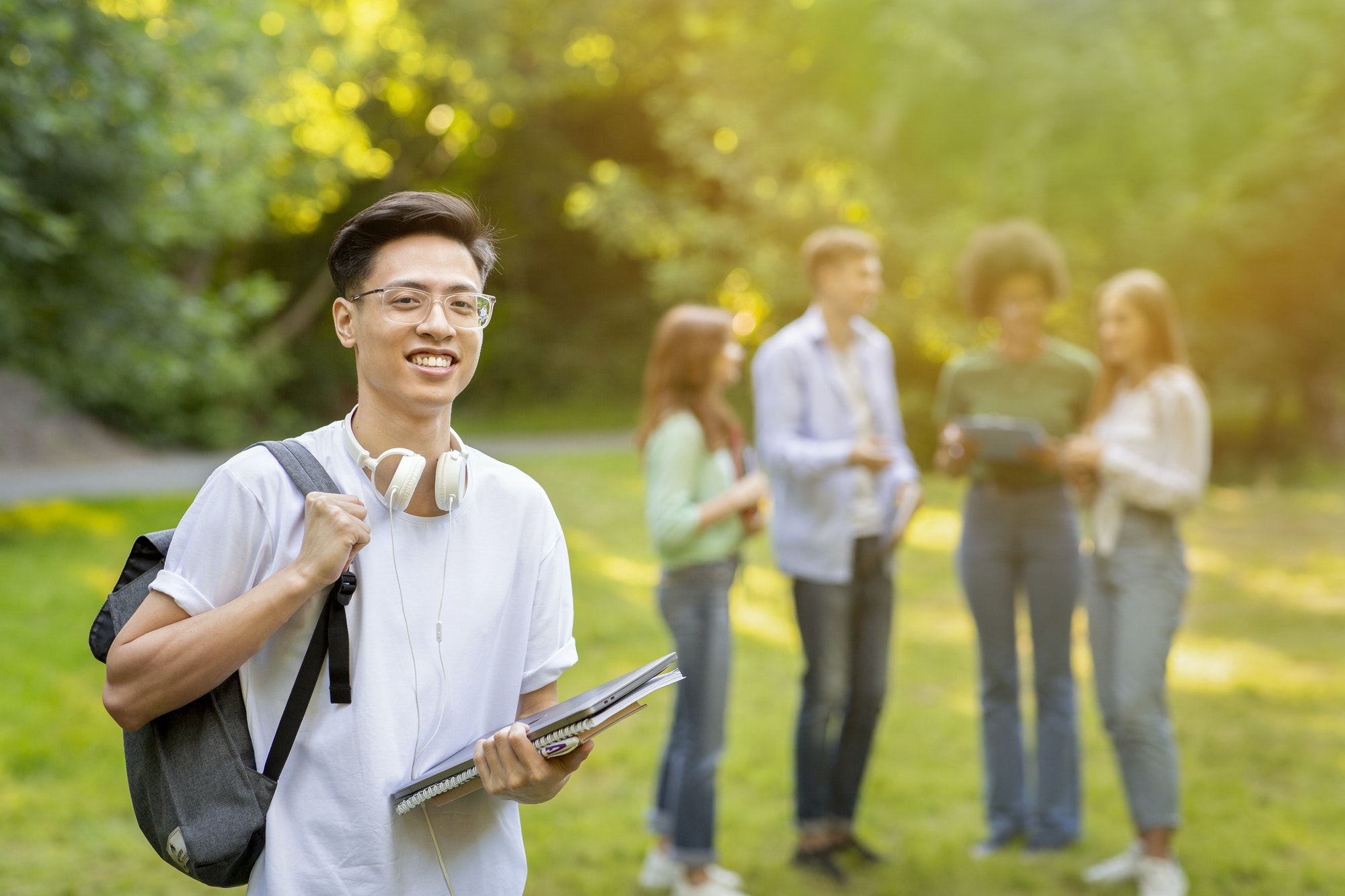 Scholarship Programs. Smiling male asian college student with backpack and workbooks outdoors